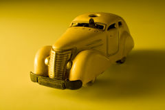 Old vintage toy car. In yellow background Stock Photos