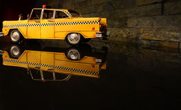 Old vintage toy metal yellow taxi car. Old vintage toy metal taxi car. Reflection of the toy taxi on the table Royalty Free Stock Photography