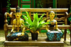 Old vintage traditional wooden statues of husband and wife with local custom fashion. Husband and wife couple wooden statues sitting together in a traditional stock photography