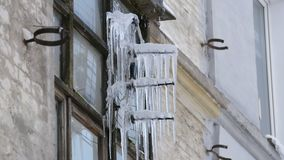 Old vintage TV antenna covered with lots of icicles in winter.