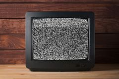 Old vintage TV set televisor on wooden table againt dark wooden wall background with no signal television grainy noise effect on. The screen stock photos