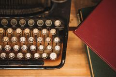 Old and vintage type writer machine and piles of books on wooden Stock Image