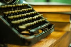 Old and vintage type writer machine and piles of books on wooden table - very selective focus. Stock Images