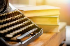 Old and vintage type writer machine and piles of books on wooden table - very selective focus. Royalty Free Stock Photography