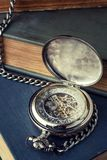 Old vintage watch, a mechanism against the backdrop of ancient b. Ooks. Tonedd photo in a dark key Stock Images