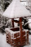 Old vintage well with a roof in the snow in winter stock photo