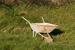 Old vintage wheelbarrow on a green grass in a garden. Royalty Free Stock Image