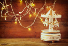 Old vintage white carousel horses with garland gold lights on wooden table. retro filtered image Royalty Free Stock Images