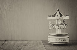 Old vintage white carousel horses on wooden table. black and white old style photo Stock Image