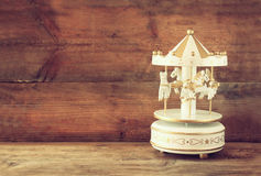 Old vintage white carousel horses on wooden table. Stock Photos