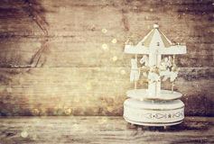 Old vintage white carousel horses on wooden table. retro filtered image Stock Image