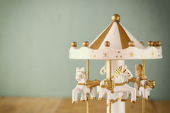 Old vintage white carousel horses on wooden table. retro filtered image Royalty Free Stock Image