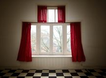 Old vintage window with big red curtains. In a old building Stock Image