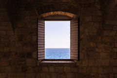 Old Vintage Window Open Shutters Looking Out at Ocean Castle For royalty free stock images