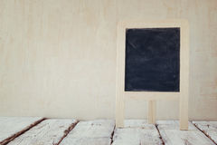 Old vintage wooden blackboard on wooden table with space for text. retro filtered image Royalty Free Stock Photo