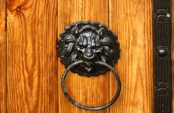 Old vintage wooden carved doors. Round metal door knobs with lions.  royalty free stock photos