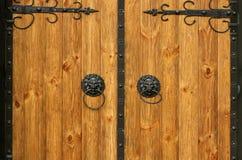 Old vintage wooden carved doors. Round metal door knobs with lions.  stock images