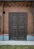 Old, vintage, wooden door in a brick wall. Royalty Free Stock Photography