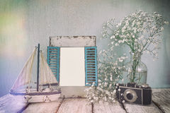 Old vintage wooden frame, white flowers, photo camera and sailing boat on wooden table. vintage filtered image