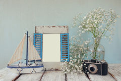 Old vintage wooden frame, white flowers, photo camera and sailing boat on wooden table. vintage filtered image Royalty Free Stock Image