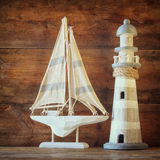 Old vintage wooden lighthouse and sailing boat on wooden table Royalty Free Stock Photo