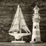 Old vintage wooden lighthouse and sailing boat on wooden table. vintage filtered image. nautical lifestyle concept. black and whit Stock Images