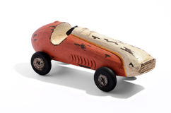 Old vintage wooden racing car. Old rustic simple handcrafted vintage wooden toy racing car painted red on a white background with shadow Royalty Free Stock Image