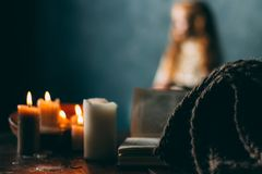 On the old vintage wooden table is a candlestick with candles. A red-haired girl in vintage clothes is sitting at the table, readi royalty free stock photography
