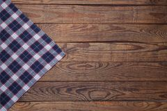 Old vintage wooden table with a red checkered tablecloth. Top view mockup. Royalty Free Stock Photo