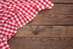 Old vintage wooden table with a red checkered tablecloth. Top view mockup. Stock Photo