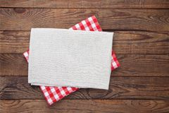 Old vintage wooden table with a red checkered tablecloth. Top view mockup. Stock Image