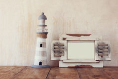 Old vintage wooden white frame and lighthouse on wooden table. vintage filtered image. nautical lifestyle concept.  Stock Images