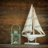 Old vintage wooden white sailing boat and lantern on wooden table Royalty Free Stock Images
