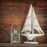 Old vintage wooden white sailing boat and lantern on wooden table. vintage filtered image. nautical lifestyle concept Royalty Free Stock Image