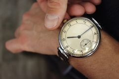 Old vintage wristwatch on men`s hand closeup. Time and deadline concept. Business and alarm background. Big retro watch. Businessman hand with luxury retro royalty free stock photos