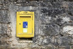 Old and vintage yellow french letterbox in France, the french public postal service. Vougeot, France - June 9, 2017: Old and vintage yellow french letterbox in Royalty Free Stock Photos