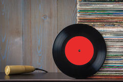Old vinyl discs and microphone. A stack of vinyl discs and an old microphone lie on a table Royalty Free Stock Photo