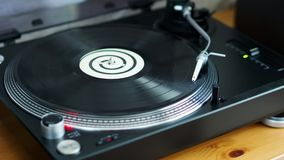 Vinyl record is spinning on a black turntable. Old vinyl record is spinning on a black turntable with a silver needle stock video footage