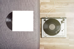 Old vinyl record and turntable. Old vinyl record in a paper case and turntable on the wooden floor Stock Photography