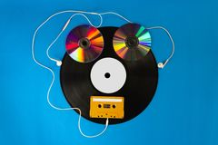 Free Old Vinyl Records And CD With Audio Cassette Tape Create Shape A Robot And Ear Headphones On Blue Background Stock Photography - 131569502