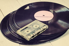 Old vinyl records and audiocassette. Toned photo Stock Photos