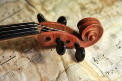Old violin on the background of notes stock photo