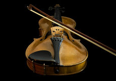 Old violin and bow, low angle view. Old violin with bow, low angle view from chinrest to scroll, black background Royalty Free Stock Images