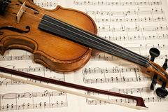 Old violin and bow on musical notes Royalty Free Stock Photography