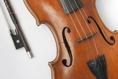 Old violin with a bow on a white background. Close-up of a violin with a bow Stock Image