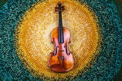Violin on a colored knitted rug. An old violin on a colored knitted rug of warm tones stock images