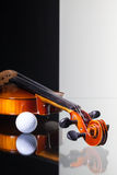 Old violin and golf ball on black and white background. Old violin and golf ball isolated on black and white background and glass desk Stock Image