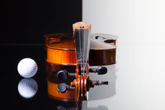 Old violin and golf ball on black and white background. Old violin and golf ball isolated on black and white background and glass desk Stock Images