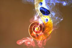 Old violin head surrended with colored smoke and flames. Music concept stock photos