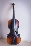 Old violin leaning against the wall Stock Photo